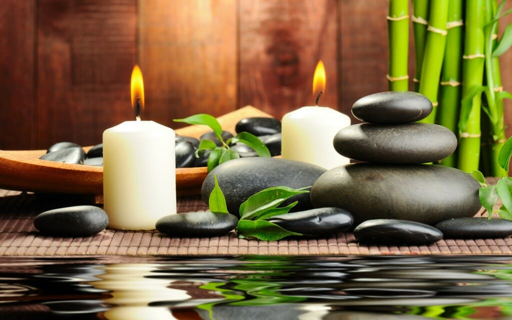 Massage stones and candles with bamboo in the background