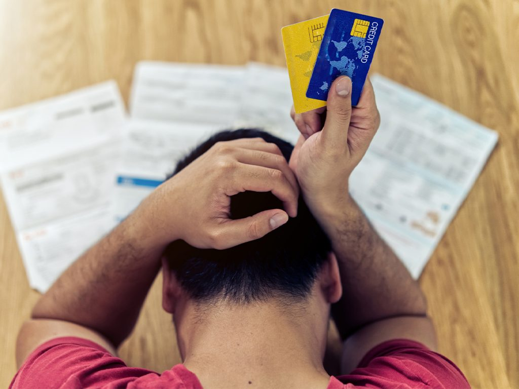 An image of a person with their head on a table holding up two credit cards.