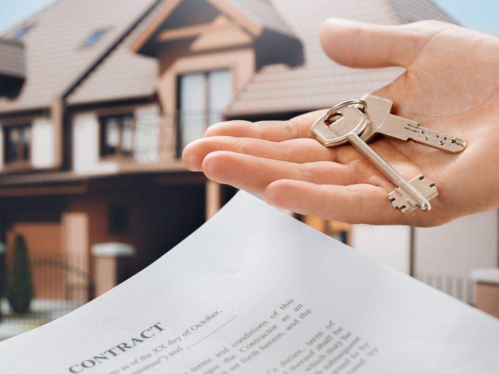 An image of a hand holding a contract and a pair of keys.